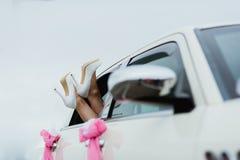 Scarpe bianche di nozze dei piedi della sposa nella finestra di automobile Fotografia Stock