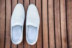 Scarpe bianche maschii sopra la tavola di legno Fotografie Stock