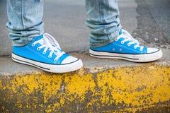 Scarpe blu nuovissime e bordo concreto giallo immagini stock