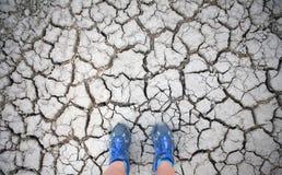 Scarpe blu su un letto di lago asciutto (selfie) Immagine Stock