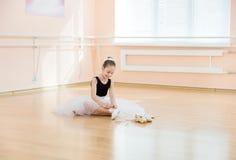 Scarpe cambianti di dancing della ballerina a pointe un mentre sedendosi sul pavimento Fotografia Stock Libera da Diritti