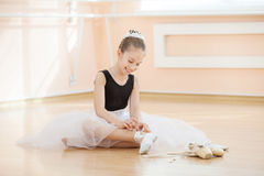 Scarpe cambianti di dancing della ballerina a pointe un mentre sedendosi sul pavimento Fotografie Stock Libere da Diritti