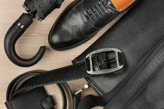 Scarpe, cartella, cinghia ed ombrello neri classici sullo scrittorio Vista da sopra Fotografia Stock Libera da Diritti
