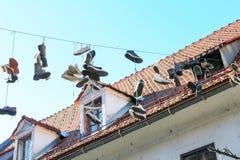 Scarpe che appendono dai laccetti su un cavo Immagine Stock