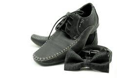 Scarpe, cinghia nera e farfallino isolati su bianco fotografia stock