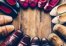 Scarpe con i vari stili delle donne e degli uomini su un pavimento di legno Fotografie Stock