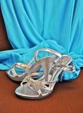 Scarpe d'argento del tacco alto con il vestito blu nel fondo Fotografia Stock