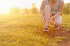 Scarpe da corsa dell'allacciamento della donna prima dell'allenamento Immagini Stock