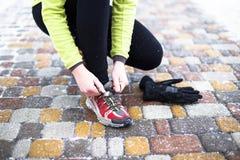 Scarpe da corsa di legatura di modello della giovane donna di sport durante Fotografie Stock Libere da Diritti