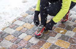 Scarpe da corsa di legatura di modello della giovane donna di sport durante l'addestramento di inverno fuori Fotografie Stock