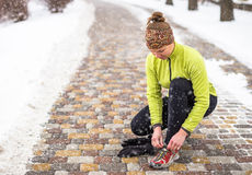 Scarpe da corsa di legatura di modello della giovane donna di sport durante l'addestramento di inverno fuori Fotografia Stock