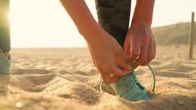Scarpe da corsa - donna che lega i laccetti sulla spiaggia sabbiosa al tramonto Movimento lento archivi video