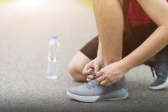 Scarpe da corsa - ginocchio dell'uomo giù con le scarpe da tennis stringa, uomo del legame del corridore che si prepara per pareg immagine stock libera da diritti