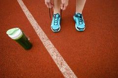 Scarpe da corsa verdi dell'allacciamento della tazza e della donna del frullato della disintossicazione prima di w Immagini Stock