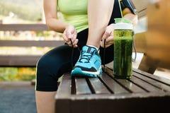 Scarpe da corsa verdi dell'allacciamento della tazza e della donna del frullato della disintossicazione prima di w Fotografia Stock