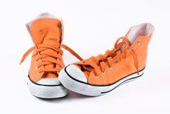 Scarpe da tennis arancioni isolate Fotografia Stock