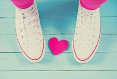 Scarpe da tennis bianche con cuore su fondo di legno blu, filtrato Fotografia Stock