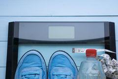 Scarpe da tennis blu, acqua, scala digitale su fondo blu Fotografia Stock