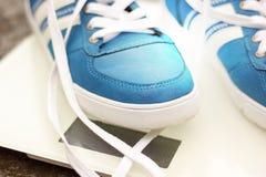 Scarpe da tennis blu del ` s degli uomini sulle scale di un quadrato bianco sulla strada asfaltata, autunno Fotografie Stock