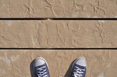 Scarpe da tennis blu sui bordi di legno coperti di sabbia Fotografia Stock Libera da Diritti