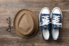 Scarpe da tennis, cappello di paglia ed occhiali da sole blu sui bordi di legno Immagini Stock