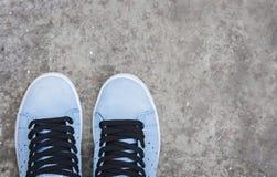 Scarpe da tennis di pelle scamosciata blu sul marciapiede immagini stock libere da diritti