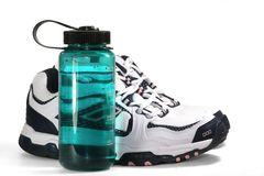 Scarpe da tennis e bottiglia di acqua di sport Immagini Stock Libere da Diritti