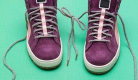 scarpe da tennis e corde del fron dell'arco su fondo verde Immagine Stock