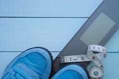 Scarpe da tennis e nastro blu sulla scala digitale Immagini Stock