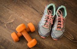 Scarpe da tennis e paia delle teste di legno arancio su fondo di legno Pesi per un addestramento di forma fisica Immagini Stock