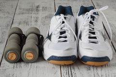 Scarpe da tennis e paia delle teste di legno su fondo di legno Pesi per Fotografia Stock