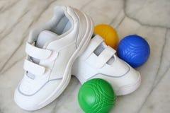Scarpe da tennis e sfere bianche fotografia stock