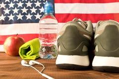 Scarpe da tennis ed accessori grigi di forma fisica sui precedenti della bandiera americana Il concetto della salute della nazion immagine stock