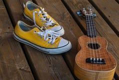 Scarpe da tennis fresche di giallo della gioventù con le ukulele su fondo di legno Fotografia Stock