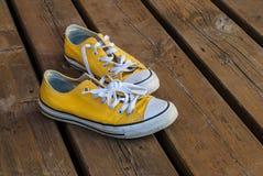 Scarpe da tennis fresche di giallo della gioventù su fondo di legno Fotografia Stock