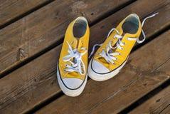 Scarpe da tennis fresche di giallo della gioventù su fondo di legno Fotografia Stock Libera da Diritti