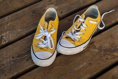Scarpe da tennis fresche di giallo della gioventù su fondo di legno Immagini Stock Libere da Diritti