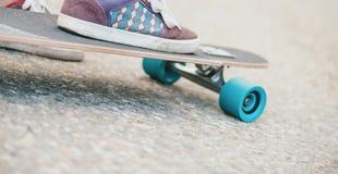Scarpe da tennis maschii della gamba sul longboard, primo piano Fotografia Stock Libera da Diritti