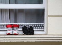 Scarpe da tennis nella finestra di vecchia casa immagini stock libere da diritti