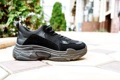 Scarpe da tennis nere sulle sogliole nere spesse contro lo sfondo delle lastre per pavimentazione fotografie stock