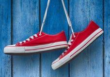 Scarpe da tennis rosse che appendono su un fondo blu di legno Fotografia Stock Libera da Diritti