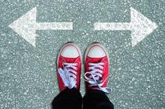 Scarpe da tennis rosse con le frecce in due direzioni Fotografie Stock Libere da Diritti