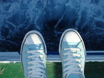 Scarpe da tennis sopra il mare Immagini Stock Libere da Diritti