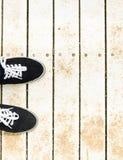 Scarpe da tennis sul fondo di legno di vecchio lerciume Immagine Stock Libera da Diritti
