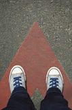 Scarpe da tennis sulla strada asfaltata con la freccia di direzione Fotografie Stock
