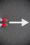 Scarpe da tennis sulla strada asfaltata con la freccia tirata di direzione Immagine Stock Libera da Diritti