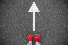 Scarpe da tennis sulla strada asfaltata con la freccia tirata di direzione Immagine Stock