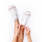 Scarpe da tennis sulle gambe delle donne Immagine Stock