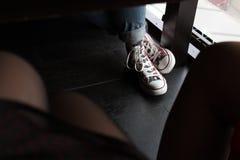 Scarpe da tennis variopinte sotto la tavola Fotografia Stock