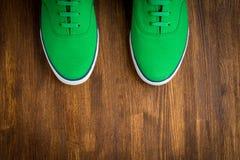 Scarpe da tennis verdi variopinte su fondo di legno Fotografia Stock